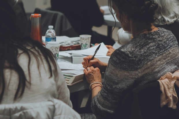 woman in a gray sweater taking notes on white paper