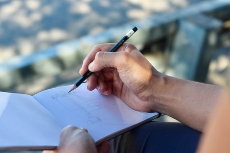 person sketching on a white pad