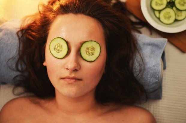 Woman Lying on White Textile With Sliced Cucumbers on Her Eyes