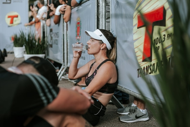 Woman Runner in Black Crop Top Sitting and Drinking Water at Marathon