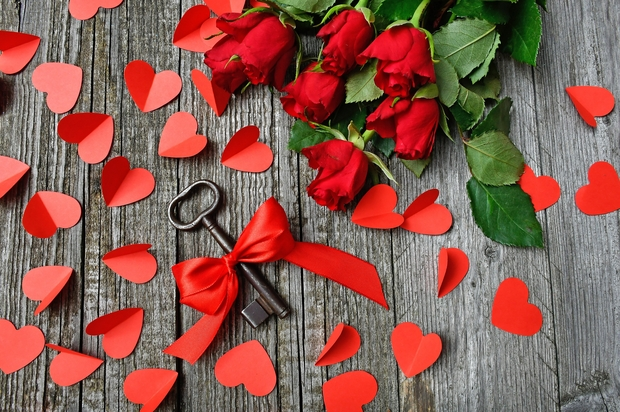 rose bouquet, red paper hearts, and key wrapped in ribbon scattered on a gray surface