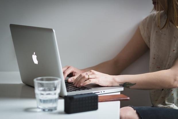 women typing on a laptop
