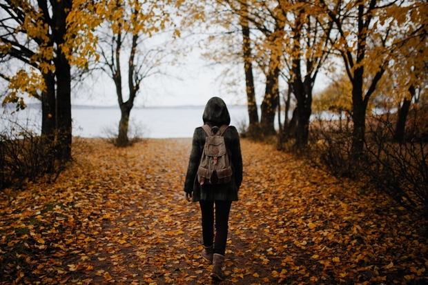 woman walking on a pathway with fall leaves