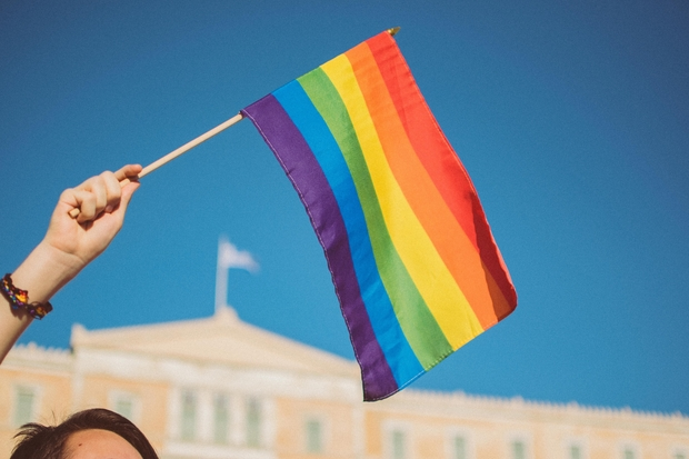girl holding pride flag with blue sky