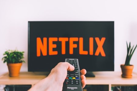 Netflix symbol on TV with a hand holding a remote