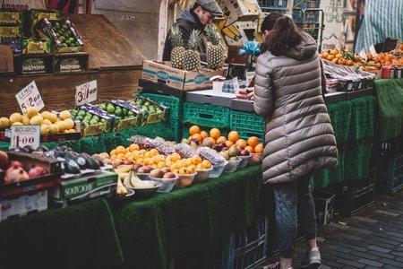 a woman shopping at a farmer's market fruit stall