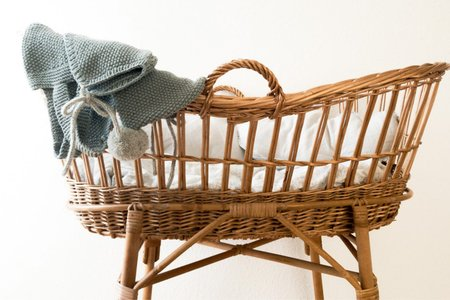 wicker baby basket with grey blanket