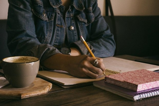 African American woman writing at a table with a cup of tea beside her
