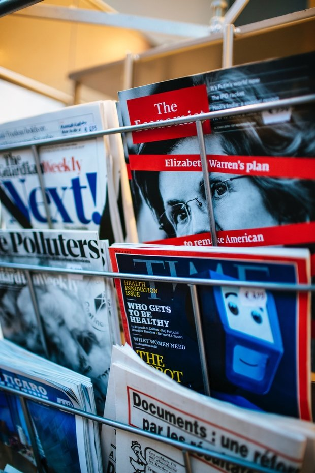 News magazine covers on a rack, including Time and The Economist