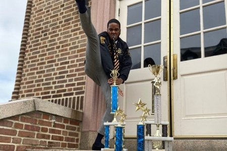 man is holding his leg up with trophies infront of him
