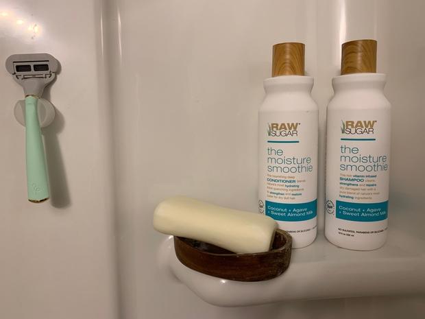 Shampoo, conditioner, bar of soap and razor in shower