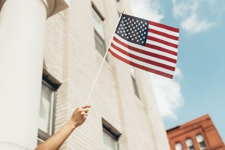 Waving a small flag in front of a building
