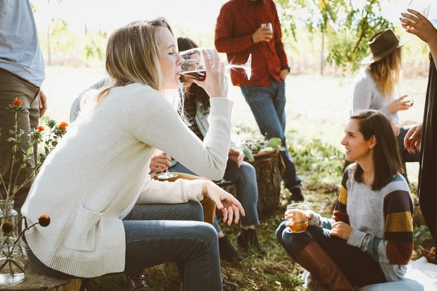 Girl drinking wine with friends