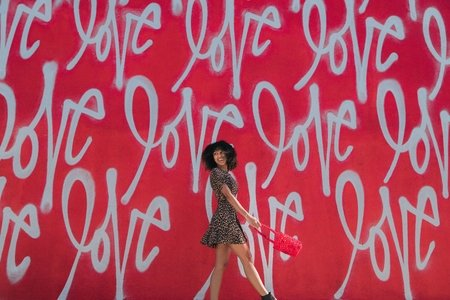 """Girl standing in front of red wall that says """"love"""""""