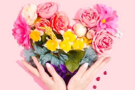 Person holding flowers in shaoe of heart with rainbow colors