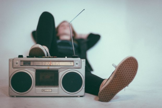 girl laying on bed behind stereo