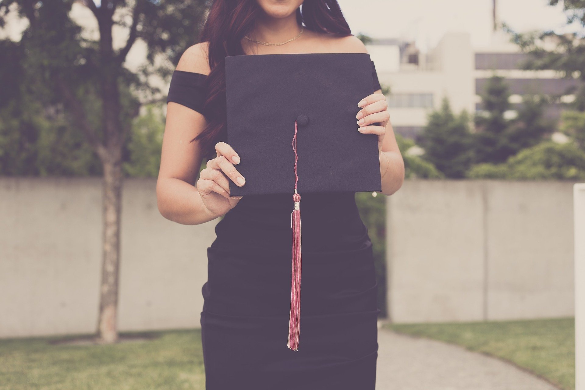 woman in black dress stands outside in front of a fence holding her graduation cap