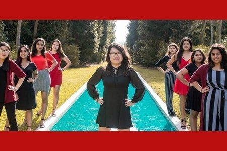 Jully standing in front of water with the rest of her executive board standing off to the sides of her