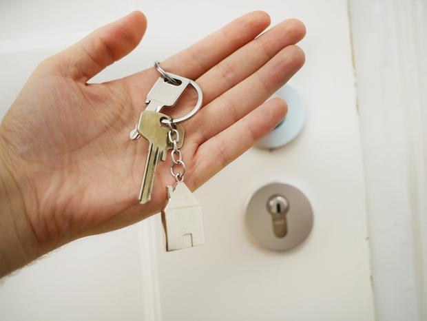 person holding a house key in their hand
