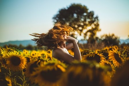 woman standing in sunflower field flipping her hair