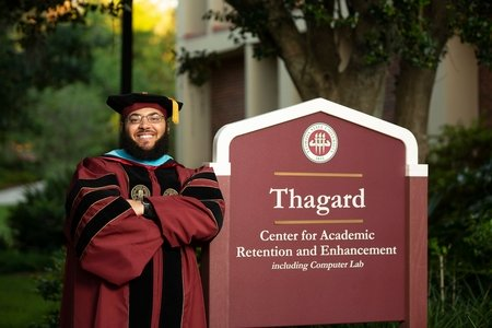 "Dr. Starke leaning on ""Thagard"" sign"