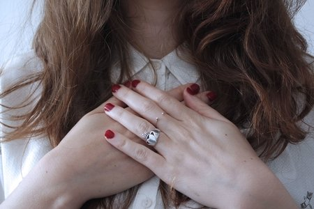 woman wearing silver-colored Claddagh ring with crossed hands and red nail polish on
