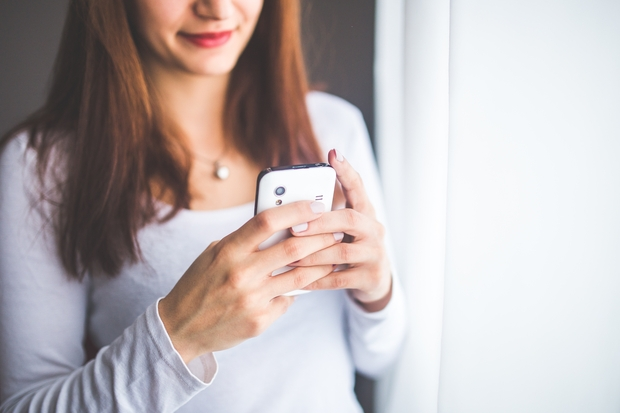 woman in a white shirt holding her cell phone in front of her