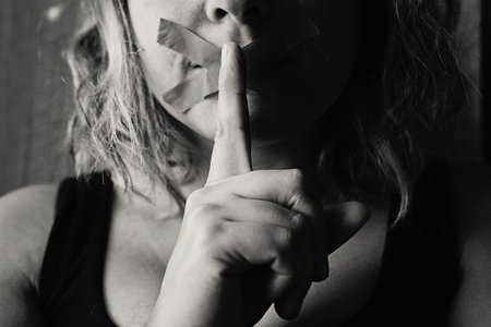 Woman placing finger over lips