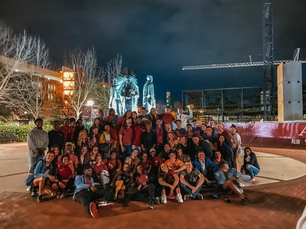 Large group of students in red shirts posing in front of a statue