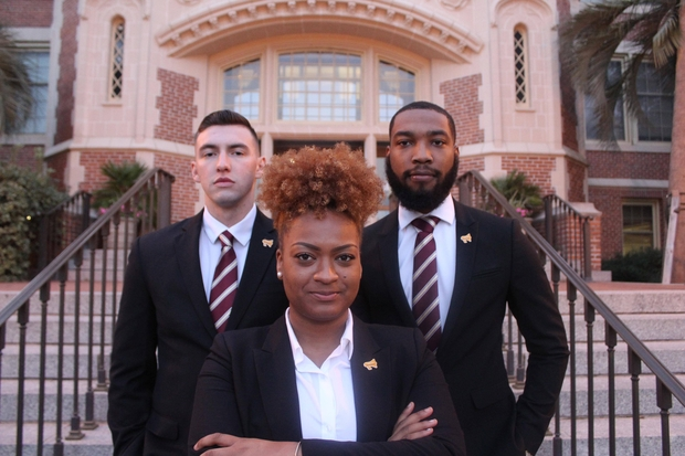 Three students in professional clothes posing seriously