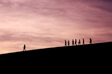 Silhouettes of people walking on a hill