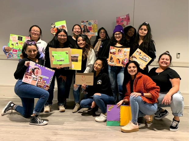 Members of woman's organization at Rutgers pose holding up handmade collages.