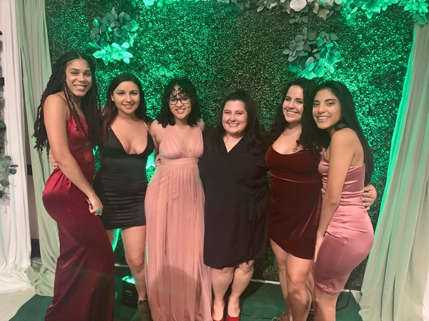 A group of women pose at a formal event in front of a green background.
