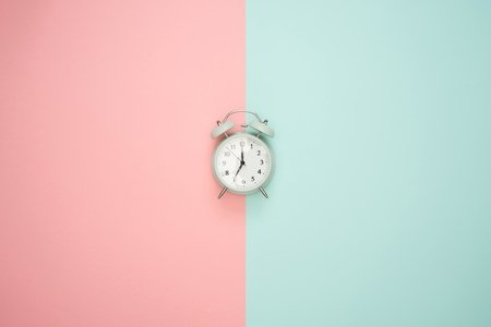 A clock in front of a pink and blue background
