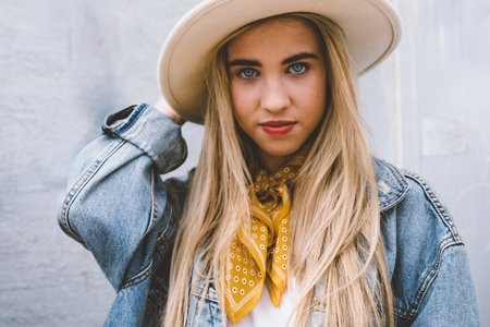 woman wearing jean jacket, hat, and bandana