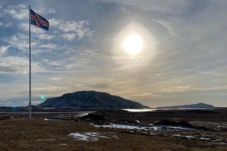 Icelandic flag with scenic background