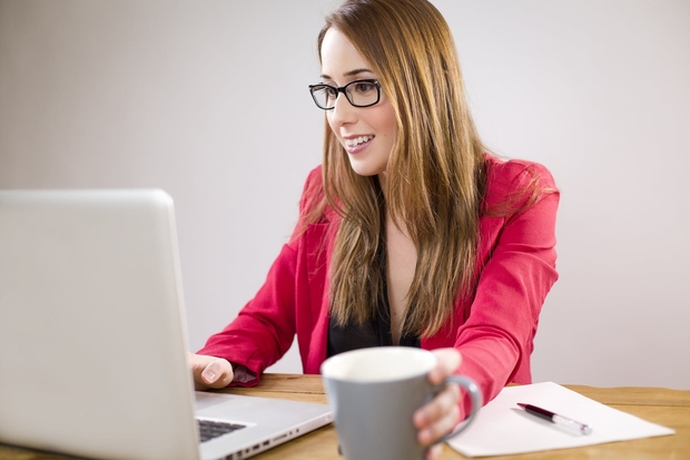 Woman in pink jacket on laptop