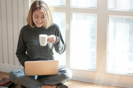 woman working on laptop while holding a mug