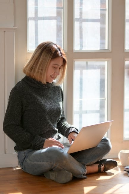 woman working on laptop by windows