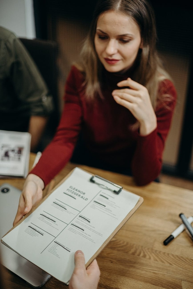 woman holding clipboard with resume on it