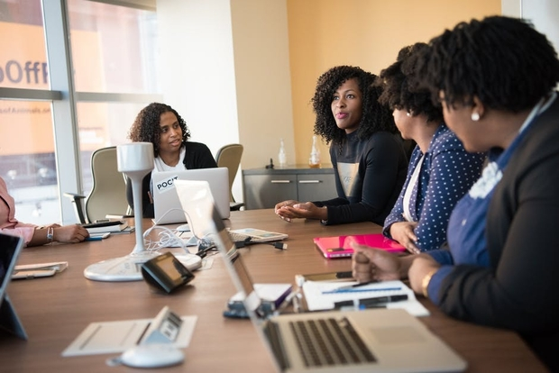 four women working at conference table job