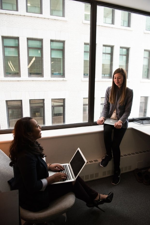 two women talking while holding laptops by the window at office