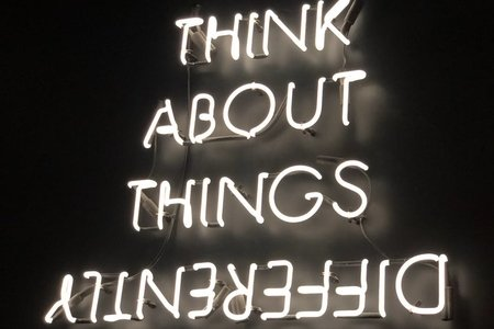 neon sign saying think about things differently