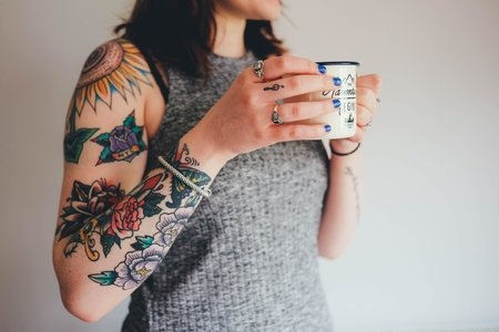 Woman with tattoos holding a mug