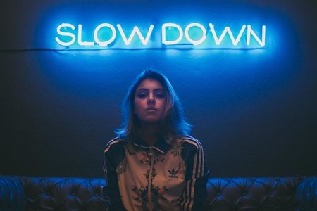 "woman sitting on a brown sofa in front of a neon sign that says ""slow down"""
