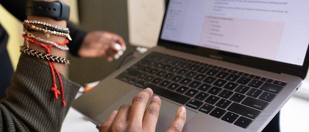 laptop, girl using it, beaded bracelets