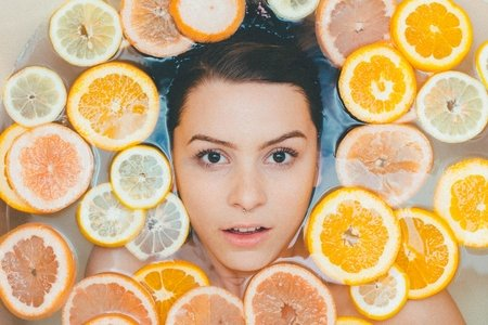 woman surrounded by lemons and oranges