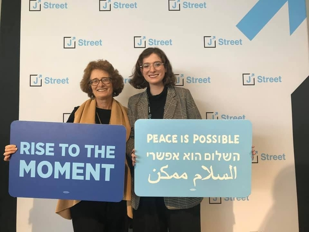 """Two women holding blue signs that say """"rise to the moment"""" and """"peace is possible"""""""