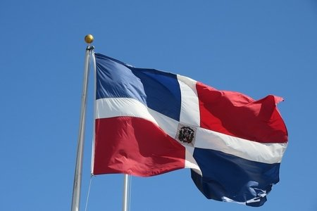 Dominican flag in front of blue sky