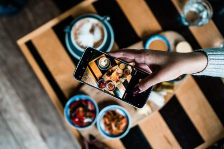 Person taking photo of food on table